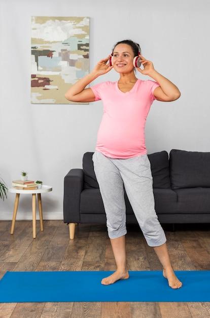 Kobieta W Ciąży Buźkę, Słuchanie Muzyki Na Słuchawkach Podczas ćwiczeń Darmowe Zdjęcia