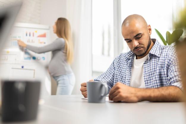 Kobieta W Ciąży Daje Prezentację, Podczas Gdy Mężczyzna Współpracownik Słucha Darmowe Zdjęcia