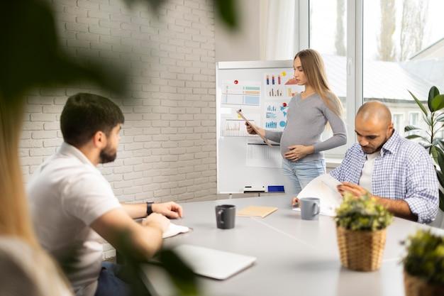 Kobieta W Ciąży Daje Prezentację, Podczas Gdy Współpracownicy Robią Notatki Darmowe Zdjęcia