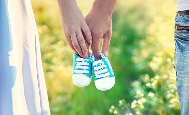 Kobieta W Ciąży I Mężczyzna Trzymają Buty Dziecięce Premium Zdjęcia