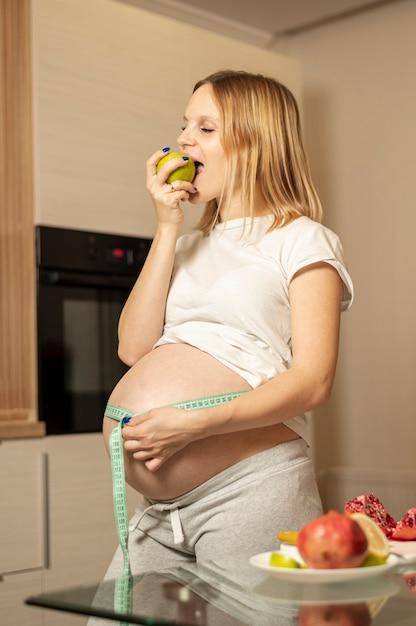 Kobieta w ciąży je jabłka i mierzy jej brzucha Darmowe Zdjęcia