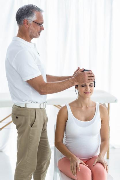 Kobieta W Ciąży Otrzymująca Masaż Głowy Od Masażysty W Domu Premium Zdjęcia