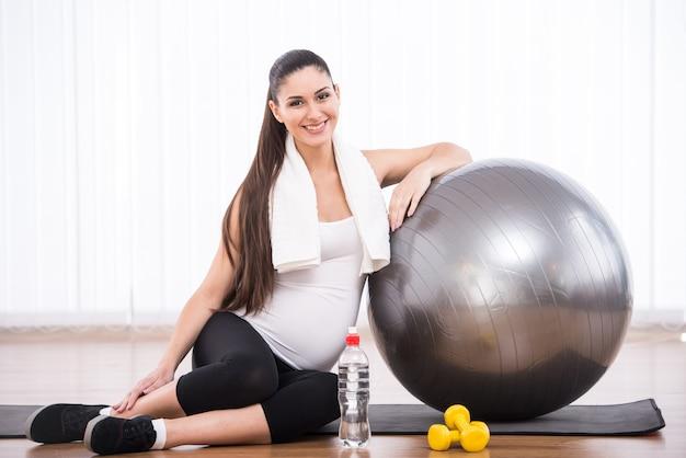 Kobieta w ciąży robi ćwiczenia z piłką gimnastyczną. Premium Zdjęcia