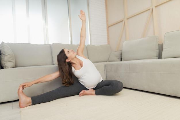 Kobieta w ciąży siedzi na lekkiej podłodze w domu. Premium Zdjęcia