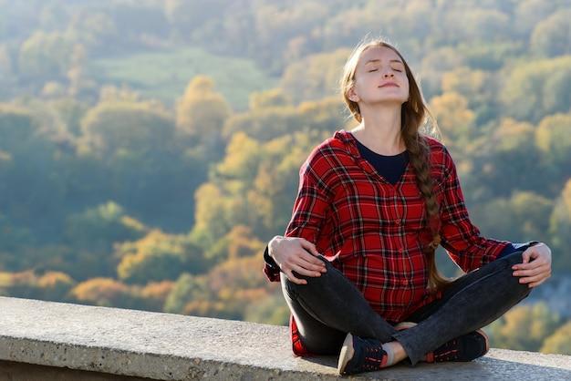 Kobieta W Ciąży Siedzi Na Wzgórzu Z Zamkniętymi Oczami. Medytacja. Las Jesienią W Przestrzeni Kosmicznej Premium Zdjęcia