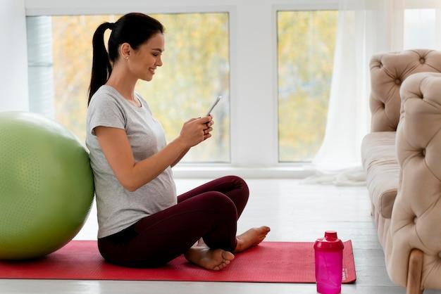 Kobieta W Ciąży Sprawdza Swój Telefon Podczas ćwiczeń Darmowe Zdjęcia