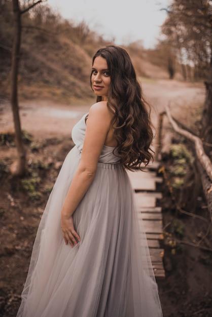 Kobieta W Ciąży W Lekkiej Długiej Sukni Premium Zdjęcia