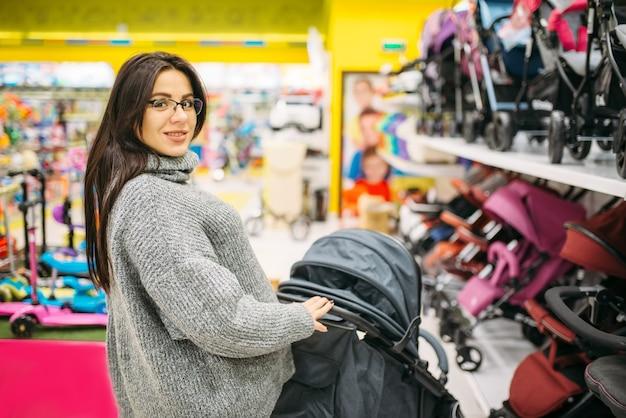 Kobieta W Ciąży W Sklepie Z Towarami Dla Noworodków, Dział Wózków Inwalidzkich. Przyszła Mama Wybiera Wózek Dla Swojego Dziecka Premium Zdjęcia