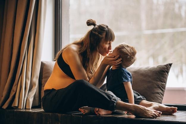 Kobieta w ciąży z synem siedzi przy oknie Darmowe Zdjęcia