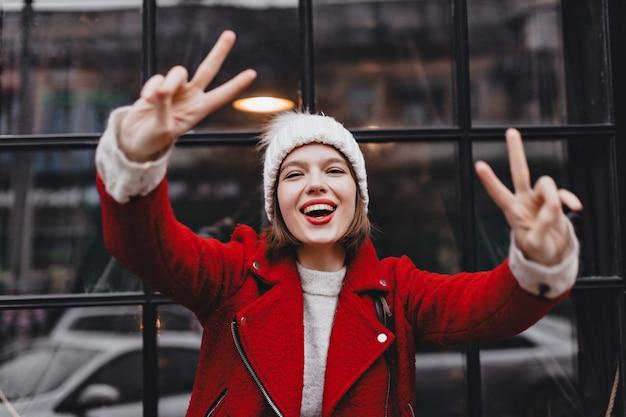 Kobieta W Czapce I Czerwonej Ciepłej Kurtce Uśmiecha Się, Pokazując Znaki Pokoju I Patrząc W Kamerę Na Tle Okna Z Czarną Drewnianą Ramą. Darmowe Zdjęcia