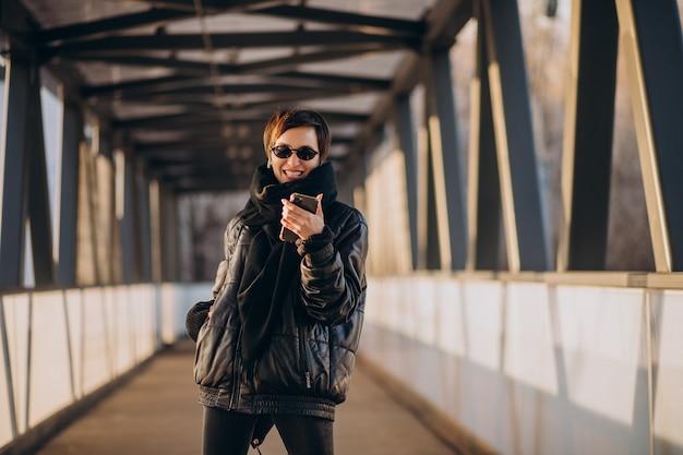 Kobieta W Czarnej Kurtce Idąc Przez Most Darmowe Zdjęcia