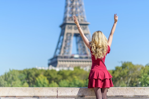 Kobieta w czerwieni sukni przy wieżą eifla w francja Premium Zdjęcia