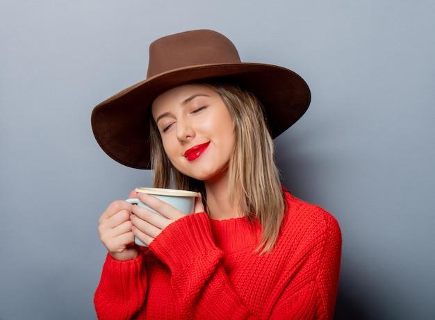 Kobieta w czerwonym swetrze i kapeluszu z filiżanką kawy Premium Zdjęcia
