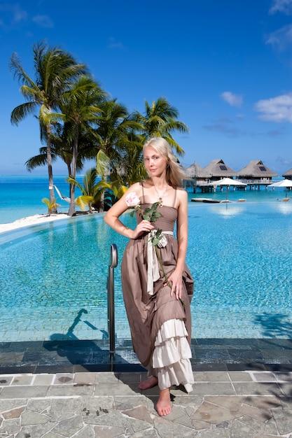 Kobieta W Długiej Sukience Przed Basenem Infiniti, Z Widokiem Na Morze Premium Zdjęcia