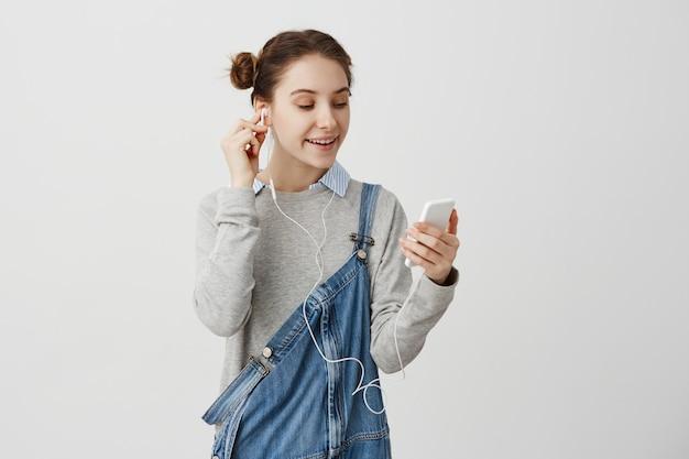 Kobieta W Drelichowym Kombinezonie Jest Zrelaksowana Przy Użyciu Smartfona, Oglądając Filmy Z Internetu. Dorosła Dziewczyna Słucha Muzyki Przez Słuchawki Z Uśmiechem. Koncepcja Technologii Darmowe Zdjęcia