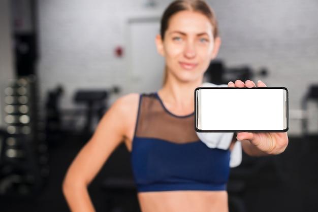 Kobieta w gym z smartphone szablonem Darmowe Zdjęcia