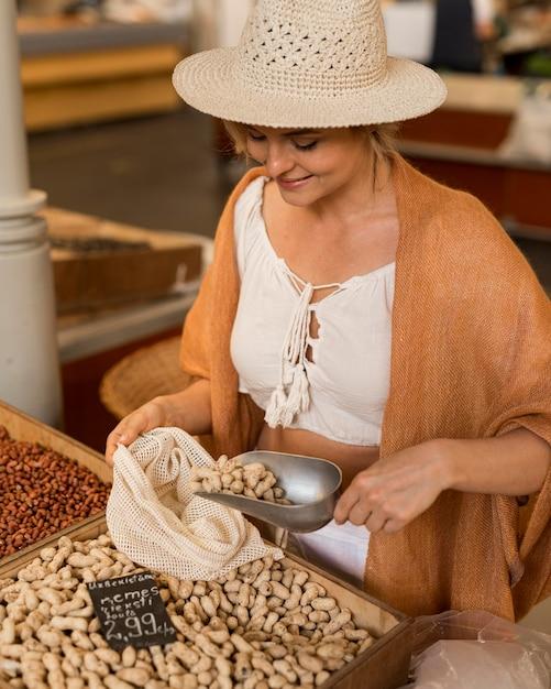 Kobieta W Kapeluszu, Biorąc Suszoną żywność Na Rynku Darmowe Zdjęcia