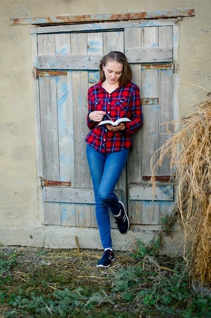 Kobieta W Kraciastej Koszuli I Dżinsach Czytająca Książkę, Plecami Do Drzwi Premium Zdjęcia