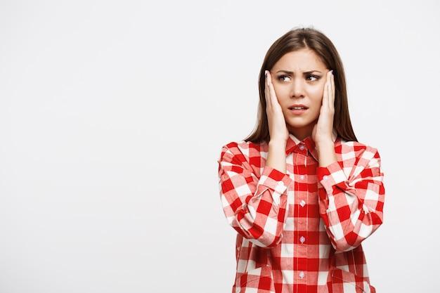 Kobieta W Kraciastej Koszuli Trzymać Ręce Na Głowie O Ból Głowy Darmowe Zdjęcia