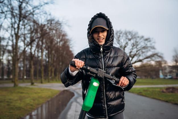 Kobieta W Kurtce Na Elektrycznej Hulajnoga W Jesień Parku. Darmowe Zdjęcia
