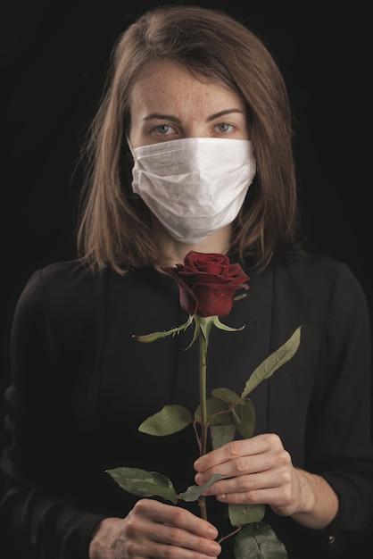 Kobieta W Masce Koronawirusa. Piękna Czerwona Róża Premium Zdjęcia