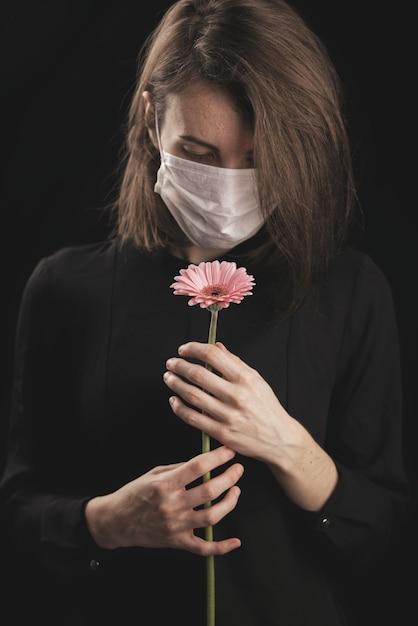 Kobieta W Masce Koronawirusa. Piękna Różowa Stokrotka Premium Zdjęcia