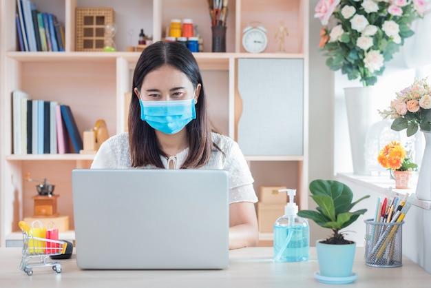 Kobieta W Masce, Która Obecnie Pracuje W Domu I Robi Zakupy Online W Celu Poddania Się Kwarantannie Podczas Wybuchu Epidemii Choroby Koronawirusa (covid-19) Premium Zdjęcia