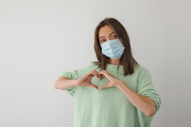 Kobieta W Masce Medycznej Ręce Serce Premium Zdjęcia