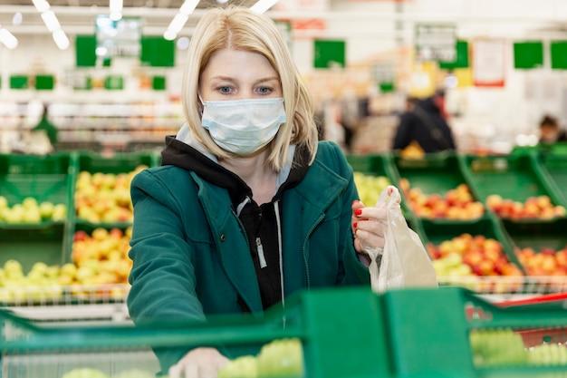 Kobieta W Masce Medycznej Wybiera Warzywa W Supermarkecie. Samoizolacja W Pandemii. Premium Zdjęcia