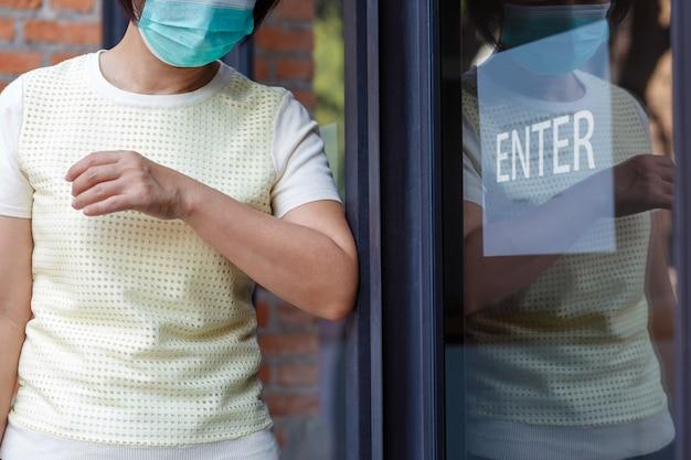 Kobieta W Masce Otwierającej Drzwi łokciem Do Infekcji Ochronnej Covid-19 Premium Zdjęcia