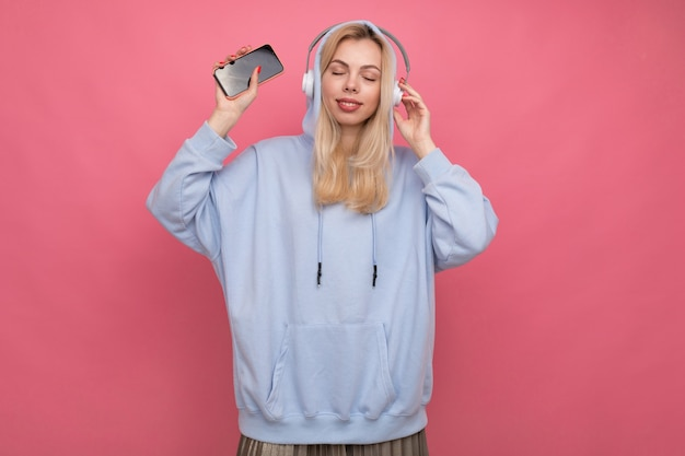 Kobieta W Modnej Bluzie Z Kapturem Słucha Muzyki Ze Swojego Telefonu Premium Zdjęcia