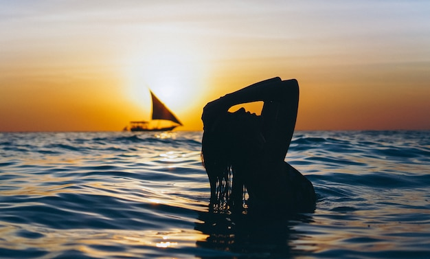 Kobieta w oceanie w czasie zachodu słońca Darmowe Zdjęcia