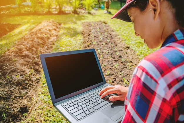 Kobieta w ogródzie z laptopem Premium Zdjęcia