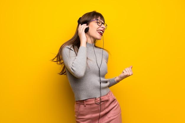 Kobieta W Okularach Na żółtej ścianie, Słuchanie Muzyki W Słuchawkach I Taniec Premium Zdjęcia