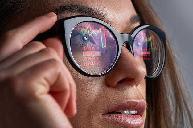 Kobieta W Okularach Patrzy Na Notowania Giełdowe I Kursy Walut Podczas Kryzysu Finansowego Premium Zdjęcia