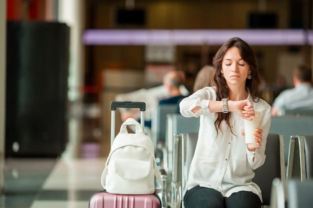 Kobieta W Poczekalni Na Lotnisku Czeka Na Lot. Turysta Kaukaski Szuka Czasu W Poczekalni Premium Zdjęcia