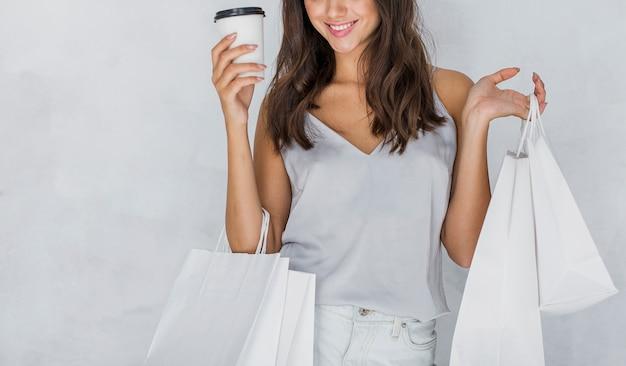 Kobieta w podkoszulku z torby na zakupy i kawy Darmowe Zdjęcia