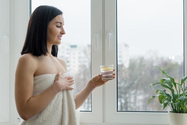 Kobieta w ręcznik ze szklanką wody z cytryną Premium Zdjęcia