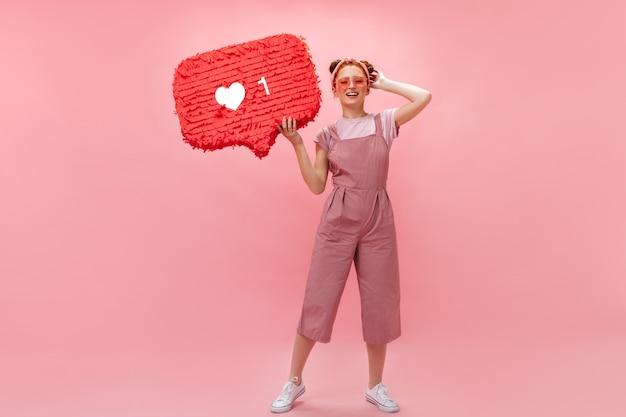 Kobieta W Różowych Okularach W Kształcie Serc Pozuje Z Podobnym Znakiem. Kobieta Ubrana W Kombinezon I Koszulkę Uśmiecha Się Na Różowym Tle. Darmowe Zdjęcia
