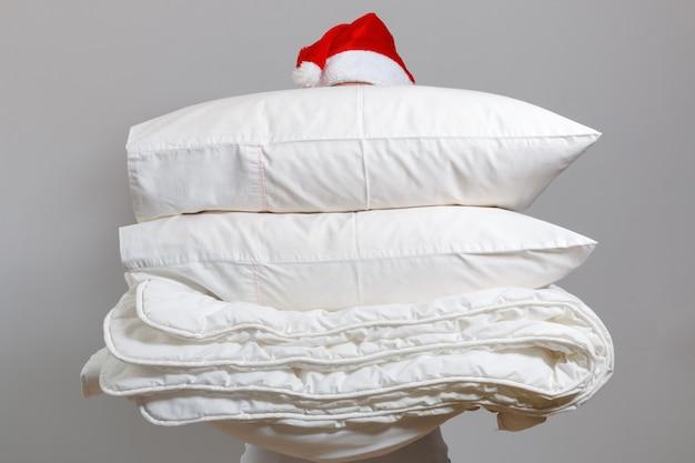 Kobieta w santa hat gospodarstwa ciepłe kołdry i poduszki z piór Premium Zdjęcia