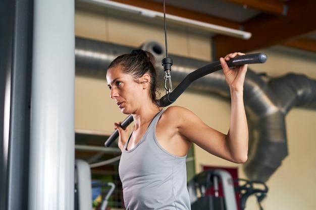 Kobieta W Sportowych Spodenkach I Szarym Podkoszulku Uprawiająca Fitness Na Siłowni ściska Dłonie Na Specjalnym Symulatorze Premium Zdjęcia
