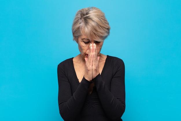 Kobieta W średnim Wieku Czująca Się Zmartwiona, Pełna Nadziei I Religijna, Modli Się Wiernie Z Zaciśniętymi Dłońmi, Błagając O Przebaczenie Premium Zdjęcia