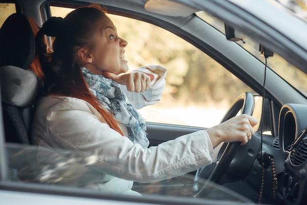 Kobieta W średnim Wieku Siedzi W Samochodzie I Narzeka Na Sytuację Na Drodze Premium Zdjęcia