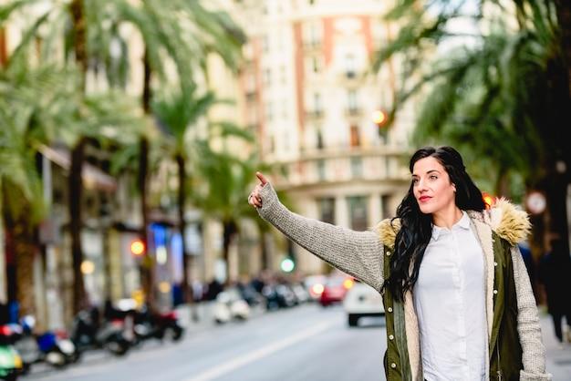 Kobieta w średnim wieku wita taksówkę z ręką podniesioną na ulicy. Premium Zdjęcia