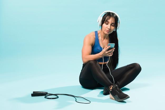 Kobieta W Stroju Siłowni, Słuchanie Muzyki W Słuchawkach Z Skakanka Darmowe Zdjęcia