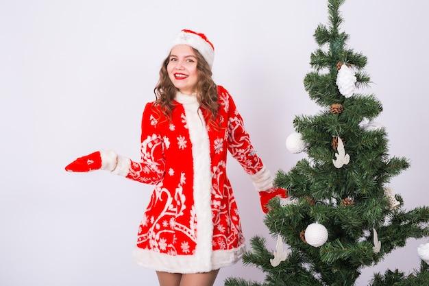 Kobieta W Stroju świętego Mikołaja W Pobliżu Choinki Premium Zdjęcia