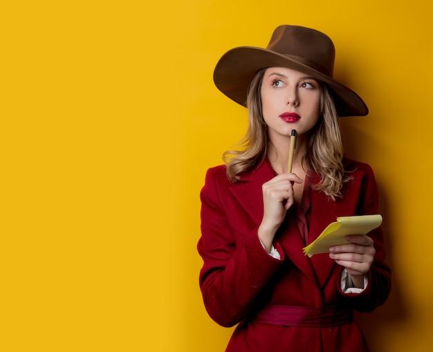 Kobieta w stylu lat czterdziestych z notatnikiem i piórem Premium Zdjęcia