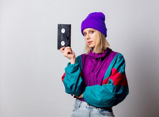 Kobieta w stylu punk z lat 90. z kasetą vhs Premium Zdjęcia