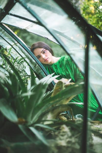 Kobieta w sukni pozuje w zielonym domu Darmowe Zdjęcia