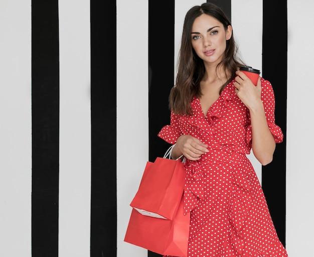 Kobieta w sukni z kawą i torby na zakupy Darmowe Zdjęcia